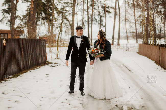 Bride and groom walking on snowy path