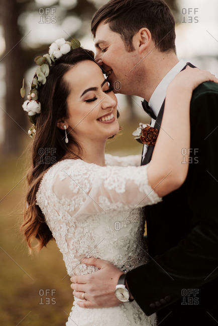 Close up of a beautiful newlywed couple embracing outdoors