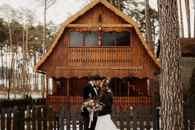 Bride and groom kissing in front of a rustic wooden building