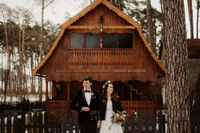 Bride and groom standing in front of a rustic wooden building