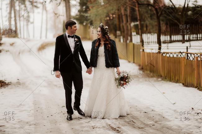 Bride and groom walking on rural wintery road