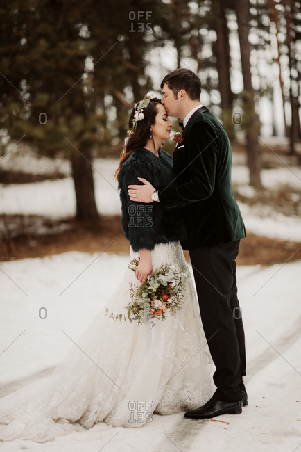 Groom kissing bride's forehead in a wintery forest setting