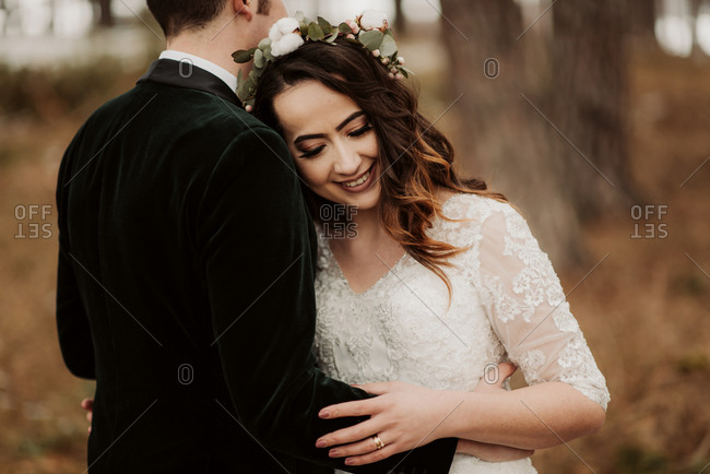 Bride and groom hugging in the woods