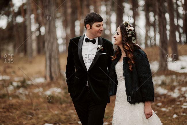 Newlywed couple walking in wintery forest
