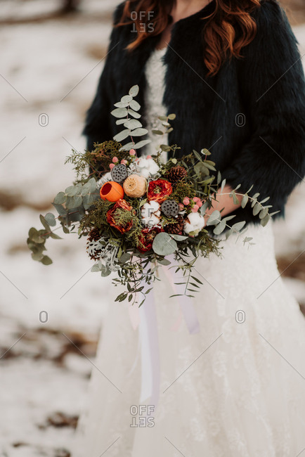 Close up of bride with bouquet in a wintery forest