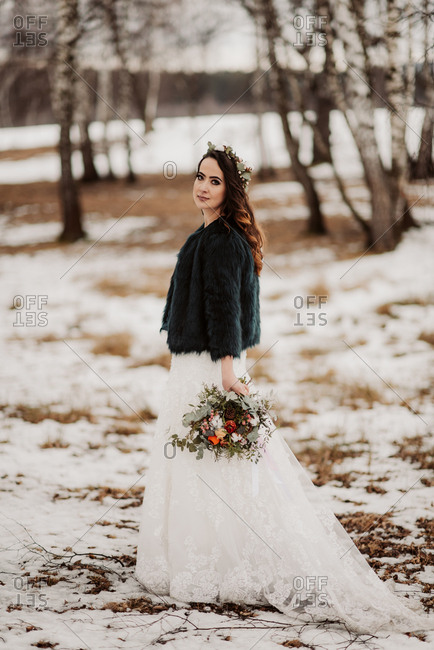 Portrait of bride holding bouquet in a wintery forest