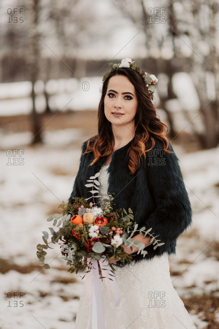 Bride holding bouquet in a wintery forest