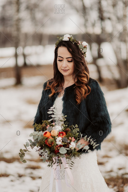 Bride with bouquet in a wintery forest