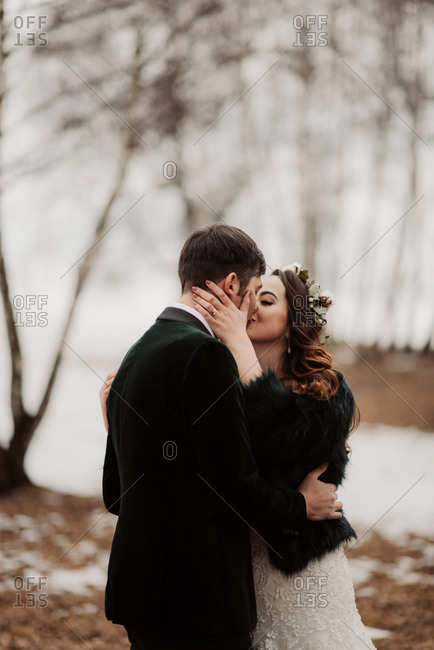 Newlywed couple kissing in wintery forest