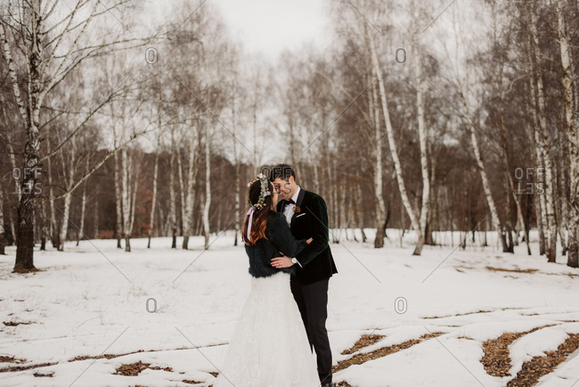 Bride and groom embraced in the forest during winter