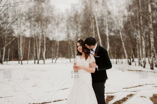 Groom whispering in bride's ear in wintery forest