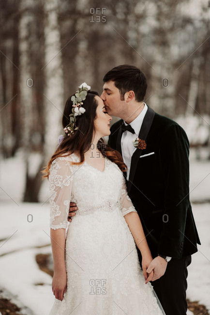 Groom kissing bride's forehead in wintery forest