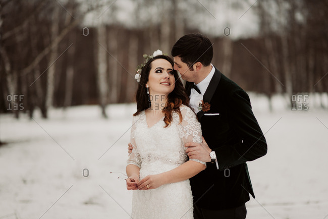 Newlywed couple standing together in wintery forest