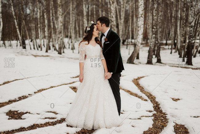 Bride and groom standing together in wintery forest