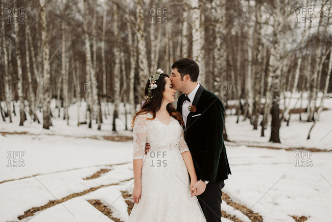 Groom kissing bride in wintery forest