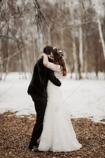 Bride and groom embraced in the woods during winter