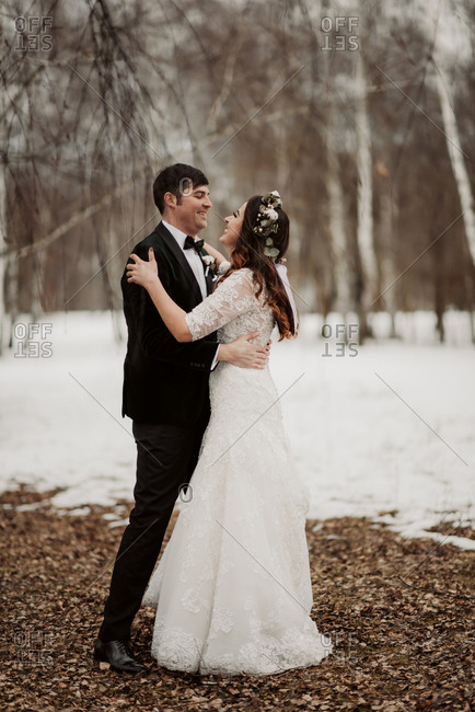 Bride and groom embraced in winter setting