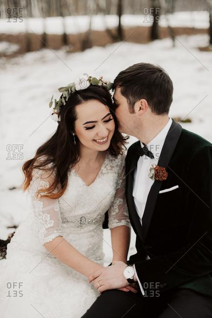 Groom whispering in bride's ear in winter setting