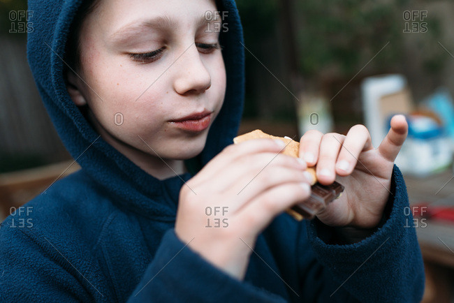 Boy biting into a s'more