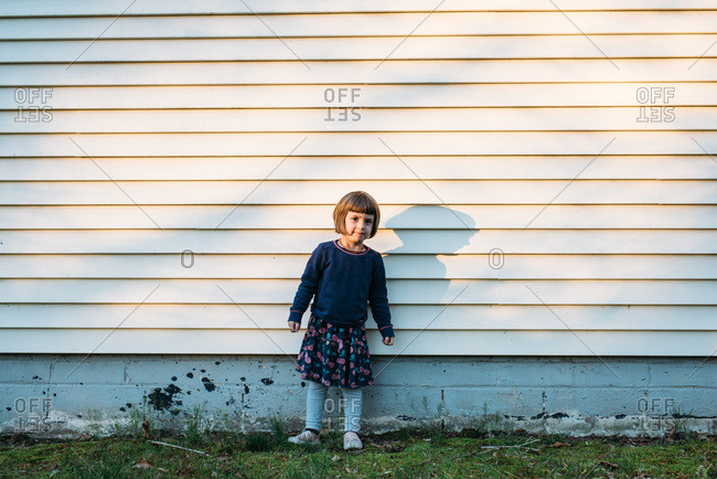 Little girl standing by the side of a house in dappled light