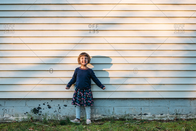 Little girl standing by the side of a house in dappled light smiling