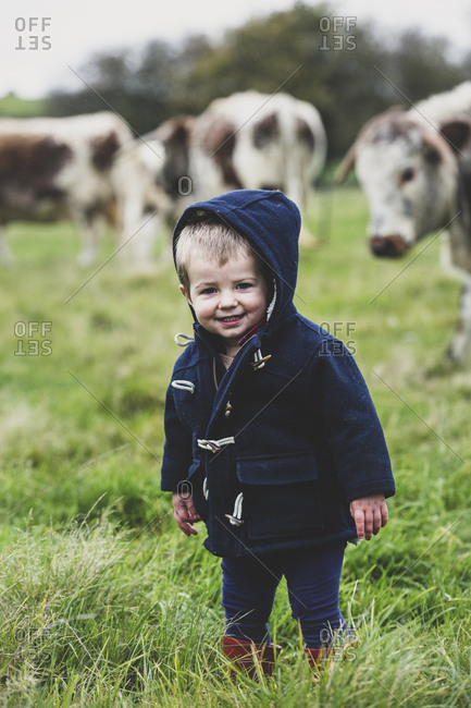 Young boy standing on a pasture, with English Longhorn cows in the background.