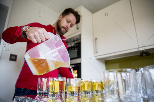 Man standing in a domestic kitchen, making jar candles.