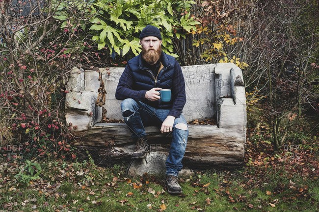 Bearded man wearing black beanie sitting on wooden bench in garden, holding blue mug, looking at camera.