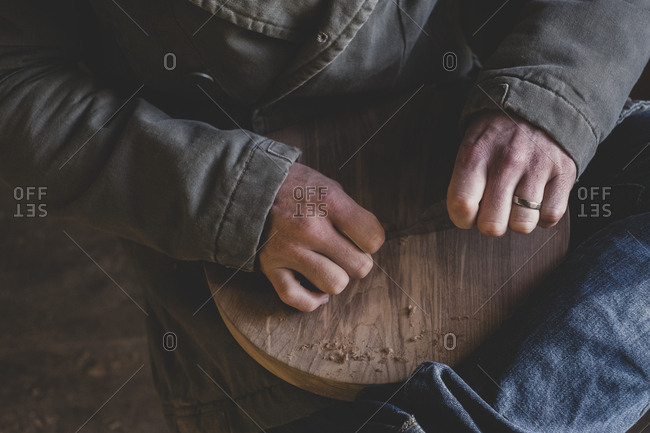 High angle close up of man sitting in workshop, holding piece of wood.