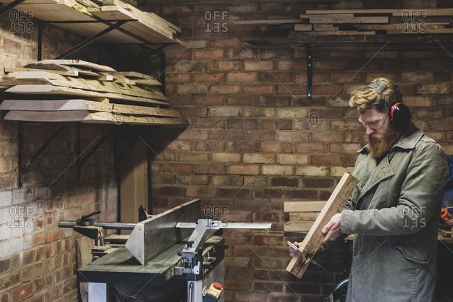 Bearded man standing in workshop, wearing ear protectors, working on piece of wood.