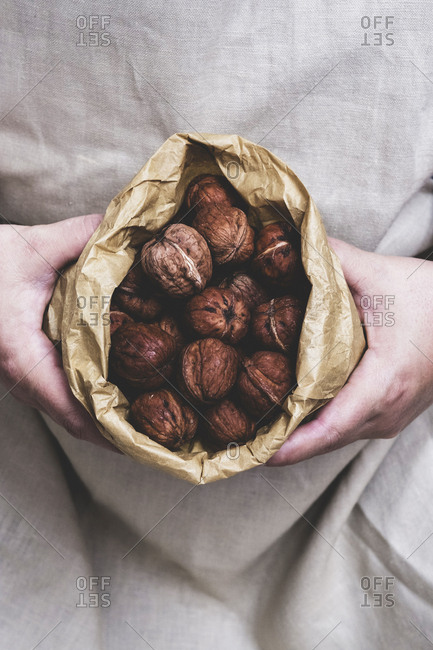 Close up of person holding brown paper bag with fresh walnuts.