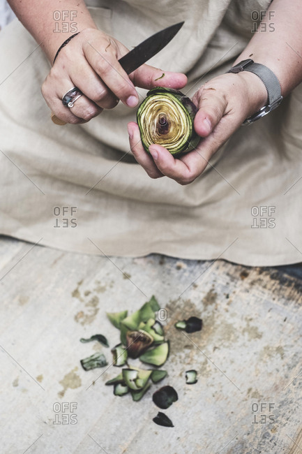 Close up of person peeling fresh artichoke with kitchen knife.
