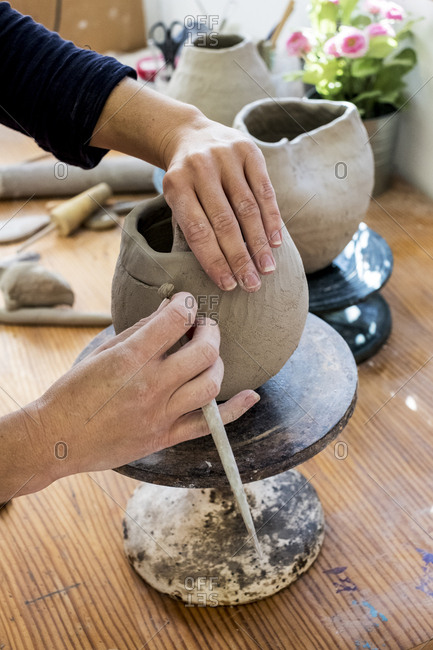 High angle close up of ceramic artist working on clay vase using pottery tool.