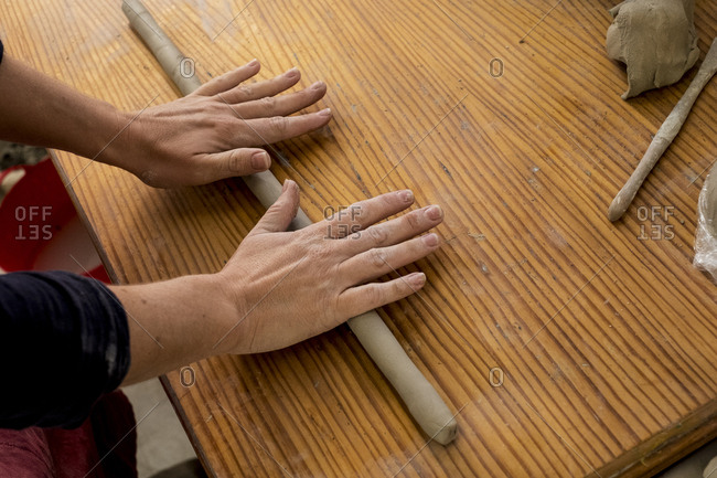 High angle close up of ceramic artist in her workshop, rolling out piece of clay on wooden table.