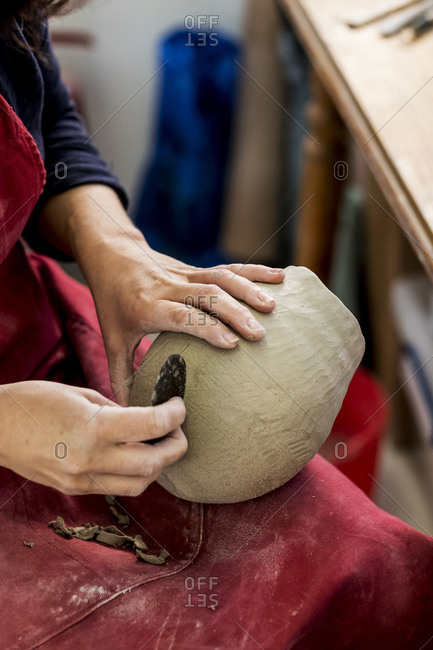 High angle close up of ceramic artist wearing red apron sitting in her workshop, working on clay vase.