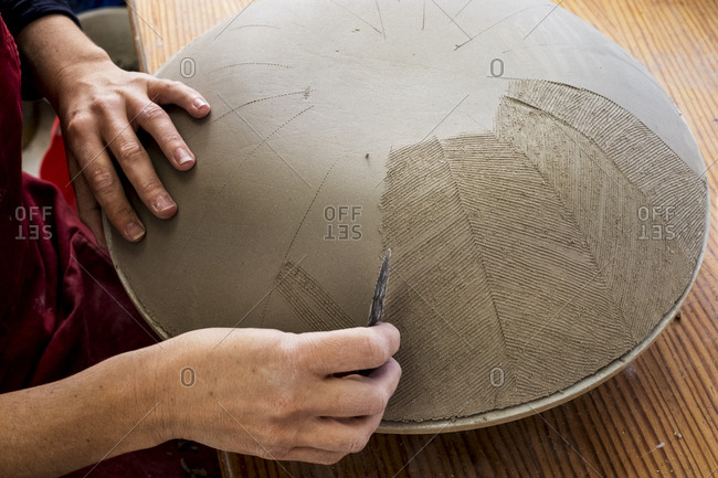 High angle close up of ceramic artist working on clay bowl, applying pattern with hand tool.