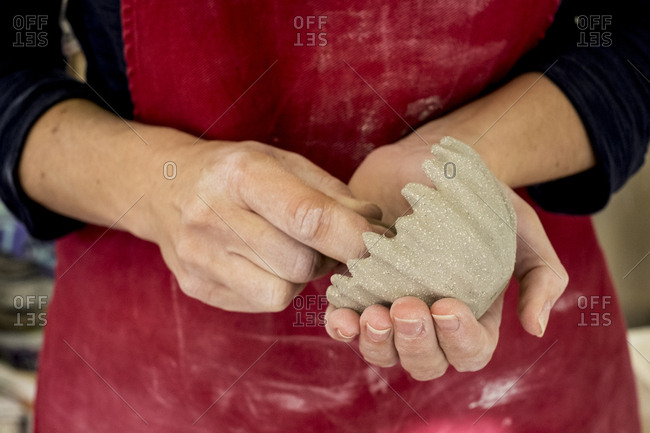 Close up of ceramic artist wearing red apron working on small clay bowl.