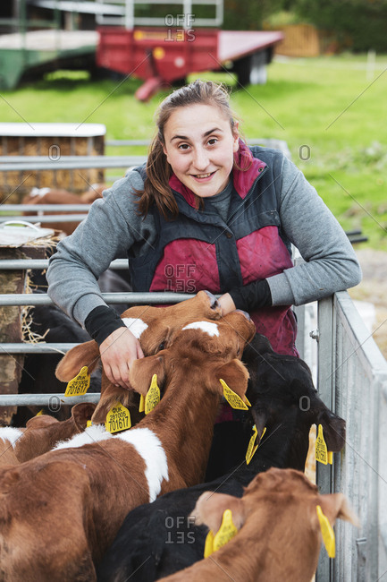 Smiling young woman standing next to metal pen with brown and black calves.