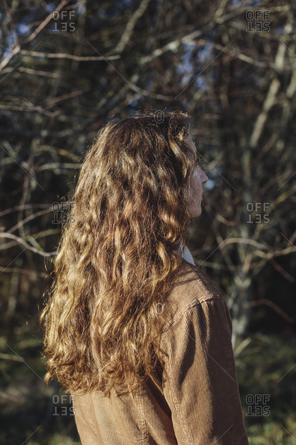 View from behind of teenage girl with long, wavy, brown hair