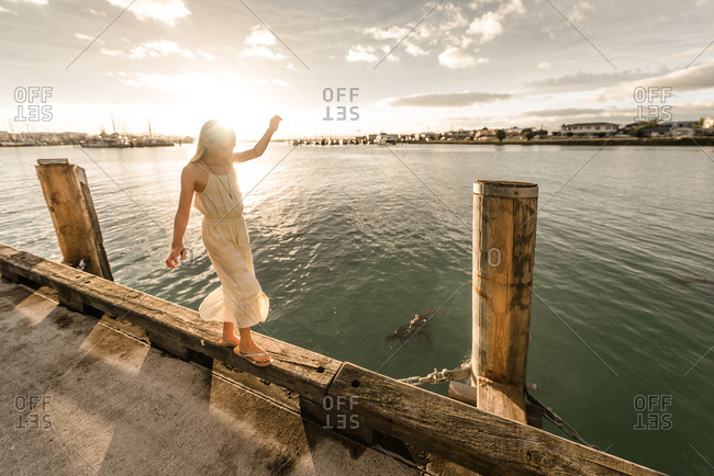 Blonde girl balancing on edge of pier