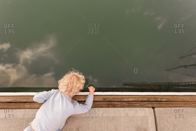 Boy looking over edge of pier
