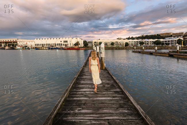 Rear view of blonde girl walking on pier