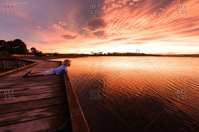 Boy looking out at colorful sunset from pier