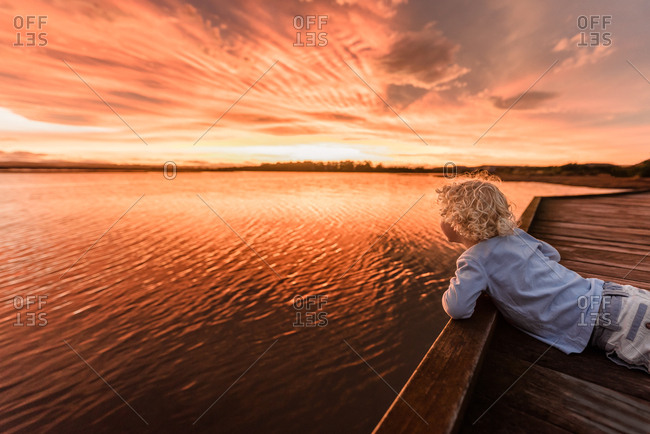 Boy looking out at colorful sunset from boardwalk
