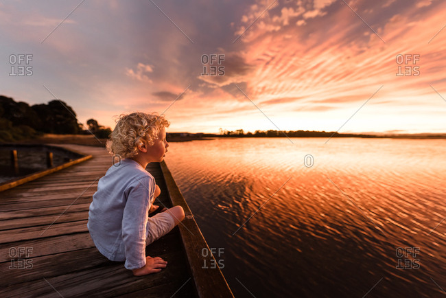 Boy sitting on boardwalk looking out at colorful sunset