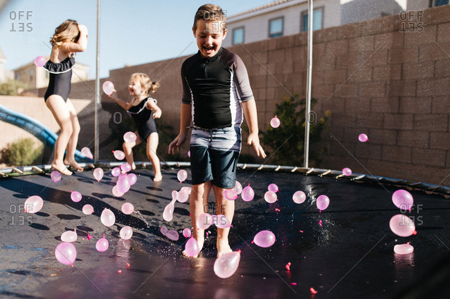 Kids jumping on a trampoline with water balloons