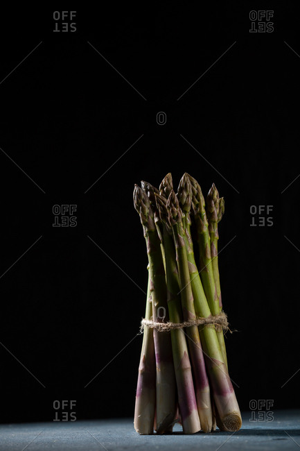 Close-up of fresh asparagus stalks on a black background