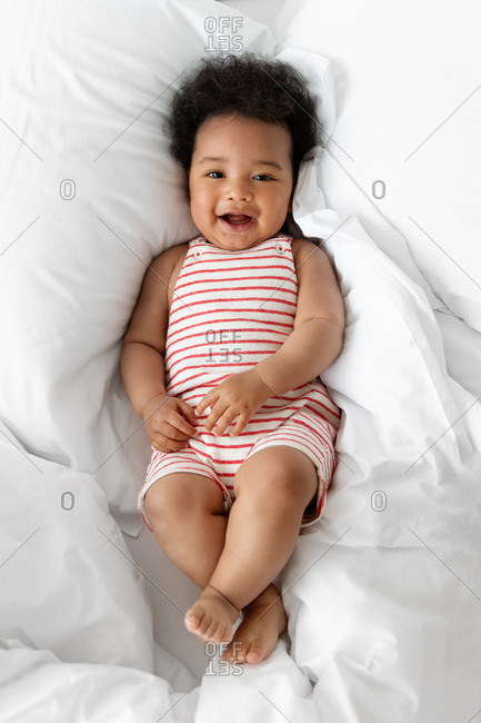 Chubby smiling baby lying on white bed