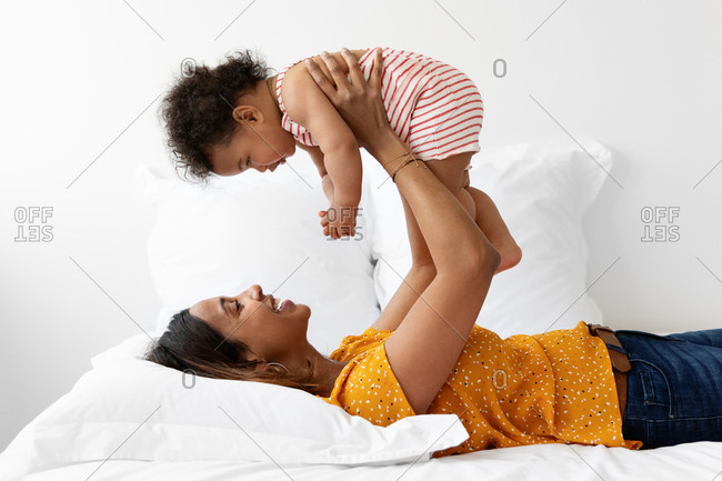Mother lifting young baby in the air while lying on bed