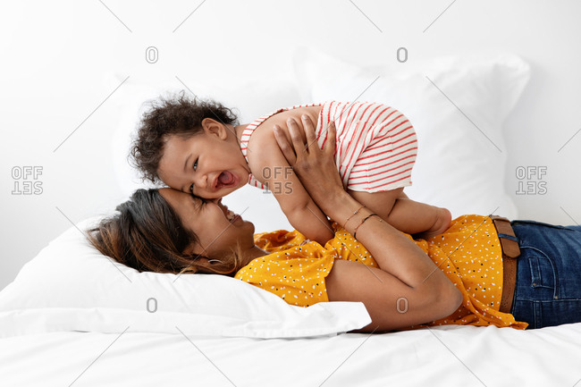 Mother holding her laughing baby against her face